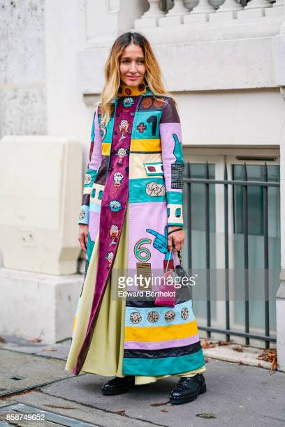 A guest wears a multi color print dress outside Valentino during Paris Fashion Week Womenswear Spring/Summer 2018 on October 1 2017 in Paris France