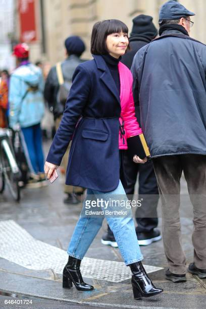 A guest wears a multicolor blue and pink jacket blue denim jeans pants and black leather boots outside the JOUR/NE show during Paris Fashion Week...