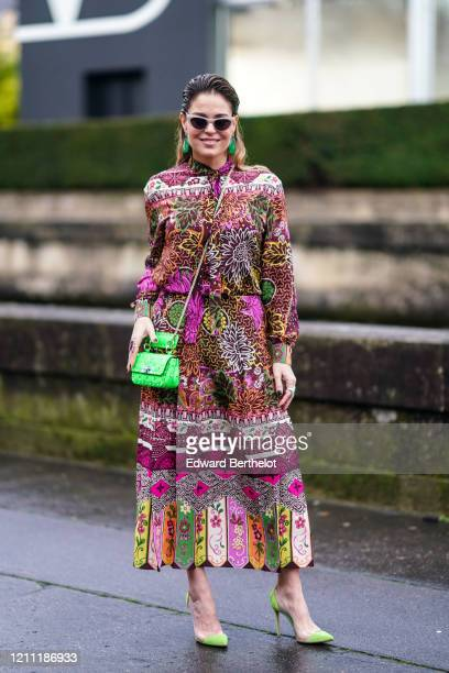 Guest wears a multicolor floral print dress, a green studded bag, green earrings, green pointy shoes, sunglasses, outside Valentino, during Paris...