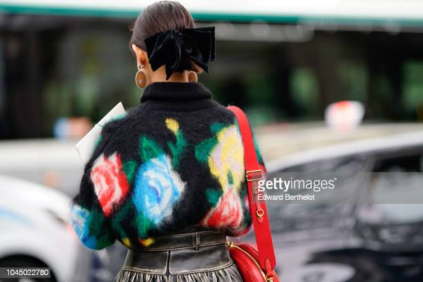 A guest wears a multicolor floral print wool pullover outside Miu Miu during Paris Fashion Week Womenswear Spring/Summer 2019 on October 2 2018 in...