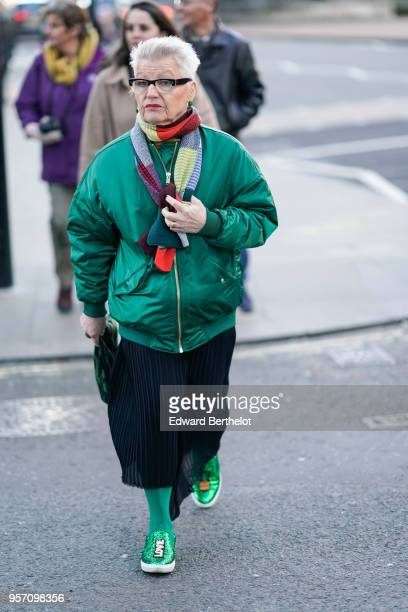 A guest wears a multicolor scarf a green bomber jacket a pleated skirt green tights green shoes with printed Love during London Fashion Week Men's...