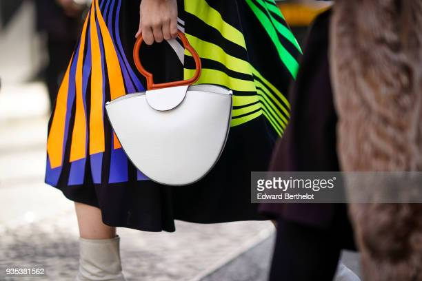 A guest wears a multicolor striped dress and holds a white semicircular bag during London Fashion Week February 2018 on February 16 2018 in London...