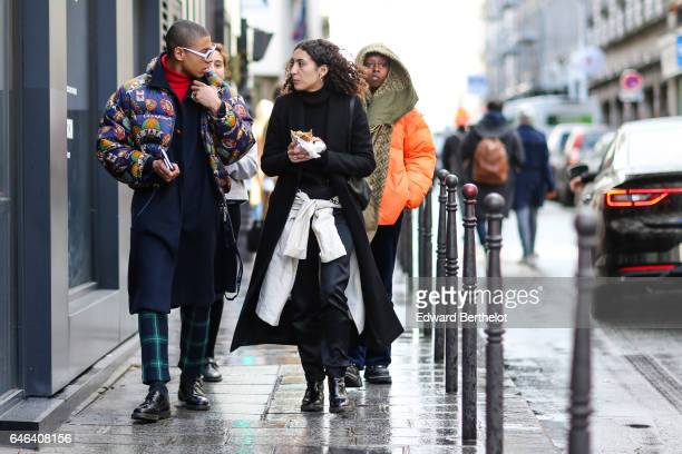A guest wears a multicolor winter puffer coat a red turtleneck top a blue long coat green checked pants and black shoes outside the AALTO show during...