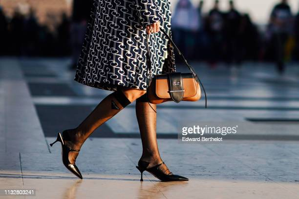 Guest wears a navy blue and white geometrical design coat, Prada pop socks, a brown Prada bag, black pointy mules, outside Rochas, during Paris...
