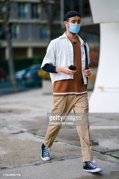 Guest wears a navy blue beanie hat, a white jacket, a brown v-neck pullover, a chain necklace, beige cuff pants, sneakers, during Paris Fashion Week...