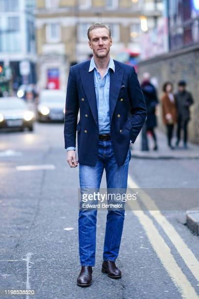 Guest wears a navy blue blazer jacket with metallic buttons, a blue shirt, a belt, blue denim pants, leather shoes, during London Fashion Week Men's...