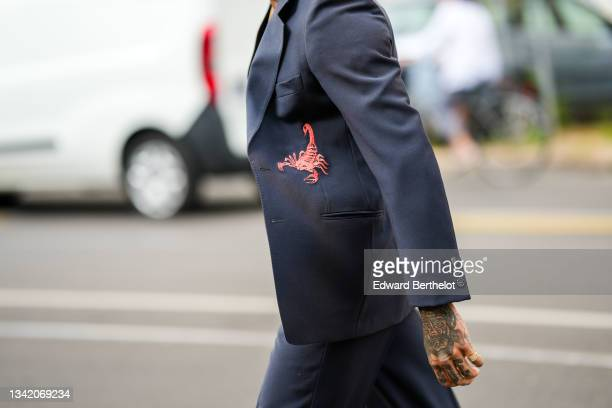Guest wears a navy blue blazer jacket with red embroidered scorpion pattern, matching navy blue suit pants, a gold ring, outside the Fendi fashion...