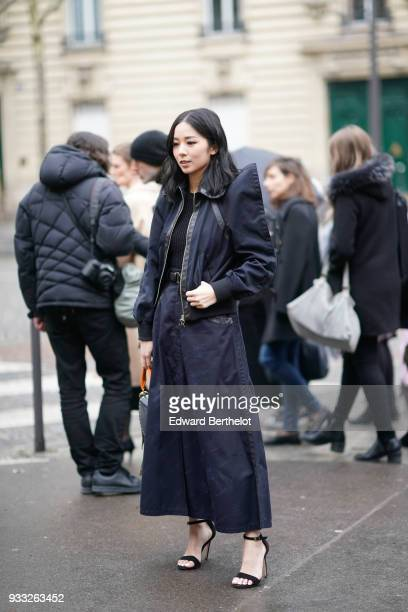 A guest wears a navy blue butterfly sleeves jacket a navy blue long flare skirt black highheeled sandals during Paris Fashion Week Womenswear...