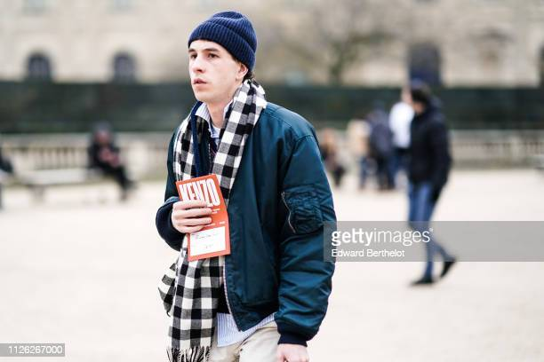 A guest wears a navy blue cap a navy blue bomber jacket a black and white checkered scarf a white shirt with baby blue stripes outside Kenzo during...