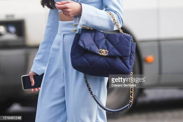 A guest wears a navy blue Chanel bag outside Chanel during Paris Fashion Week Womenswear Fall/Winter 2020/2021 on March 03 2020 in Paris France