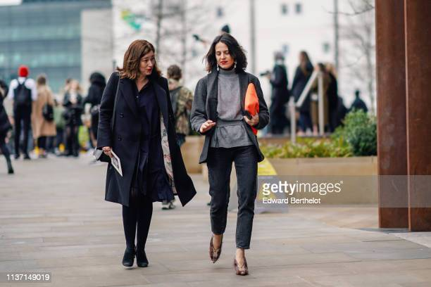 Guest wears a navy blue coat, black shoes ; A guest wears earrings, a grey top, a light grey turtleneck, a grey jacket, black pants, an orange bag,...