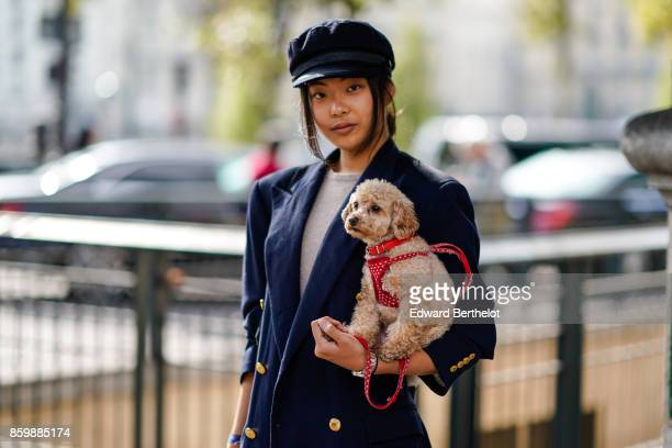 A guest wears a navy blue hat a navy blue double breasted jacket with brass buttons and holds a dog pet outside the Dries Van Noten show during Paris...