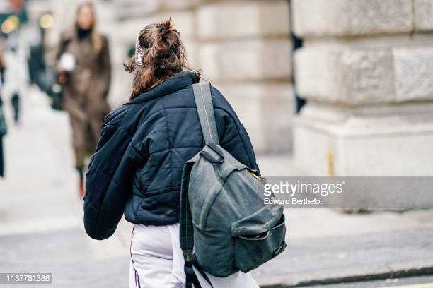 A guest wears a navy blue padded jacket a black backpack during London Fashion Week February 2019 on February 16 2019 in London England