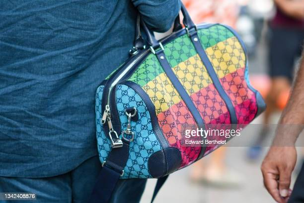 Guest wears a navy blue shiny leather and GG multicolored monogram fabric handbag from Gucci, outside the Tod's fashion show during the Milan Fashion...