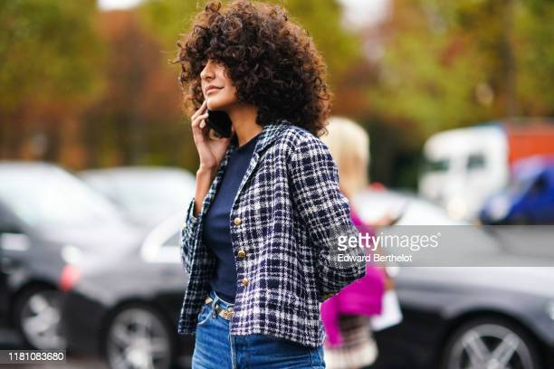 Guest wears a navy blue top, a black and white checkered Chanel jacket, blue denim pants, outside Chanel, during Paris Fashion Week - Womenswear...