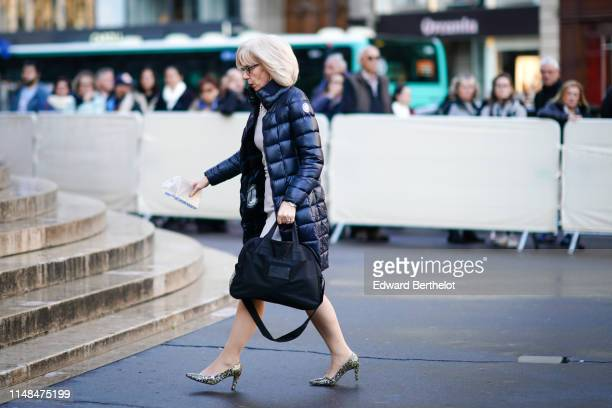A guest wears a navy blue Trussardi puffer coat a light grey dress with a rhinestone embellished collar a large black bag leopard print pointy heeled...