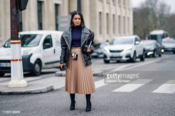 A guest wears a navy blue turtleneck a black leather oversize jacket a peach color pleated skirt with several key holders at the waist black pointy...