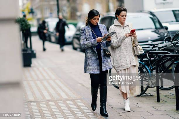 A guest wears a navy blue turtleneck a blue and grey checkered jacket a black bag black pants black pointy boots A guest wears a beige oversize knit...