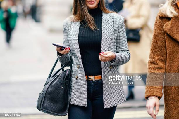 A guest wears a navy blue turtleneck navy blue pants a grey checkered jacket A Hermes belt a navy blue bag during London Fashion Week February 2019...