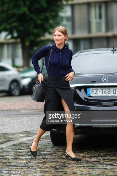 Guest wears a navy blue with white print pattern scarf as a hair elastic, a navy blue ribbed polo shirt, a black shiny leather crossbody bag, a black...