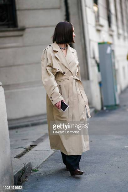 A guest wears a necklace a beige trench coat black pants brown crocodile pattern boots outside Bottega Veneta during Milan Fashion Week Fall/Winter...