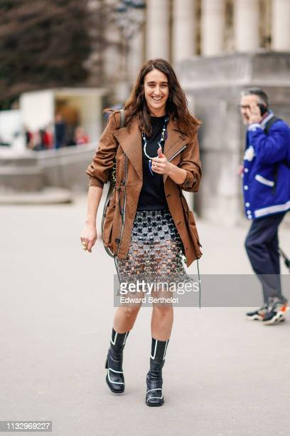 Guest wears a necklace, a brown houndstooth jacket, a black top, a transparent vinyl and metal mesh skirt, black boots with white inserts, outside...