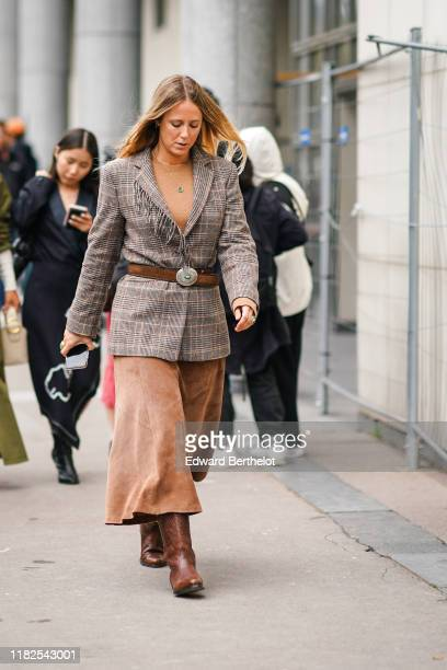 Guest wears a necklace, a camel top, a grey and brown Prince of Wales check fringed jacket, a brown cowboy belt, a light brown leather skirt, brown...