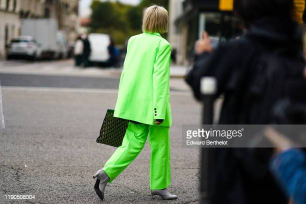 A guest wears a neon green jacket pants gray shoes outside Ann Demeulemeester during Paris Fashion Week Womenswear Spring Summer 2020 on September 26...