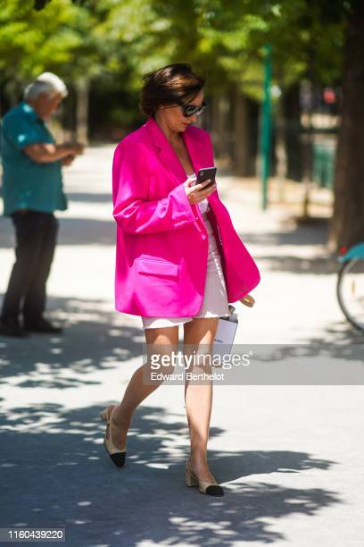 Guest wears a neon pink blazer jacket, a white dress, Chanel sling, outside Chanel, during Paris Fashion Week -Haute Couture Fall/Winter 2019/2020,...