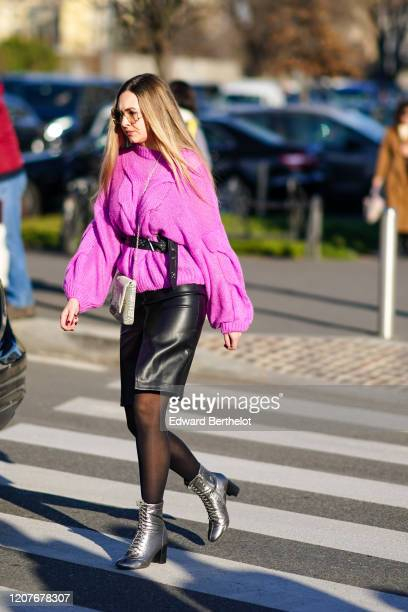 A guest wears a neon pink oversized wool pullover a black leather skirt black tights silver shoes outside Prada during Milan Fashion Week Fall/Winter...