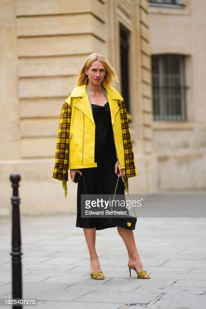 Guest wears a neon yellow shiny leather fringed coat with checkered sleeves and back, diamond earrings, a black off-shoulder midi dress, a black...