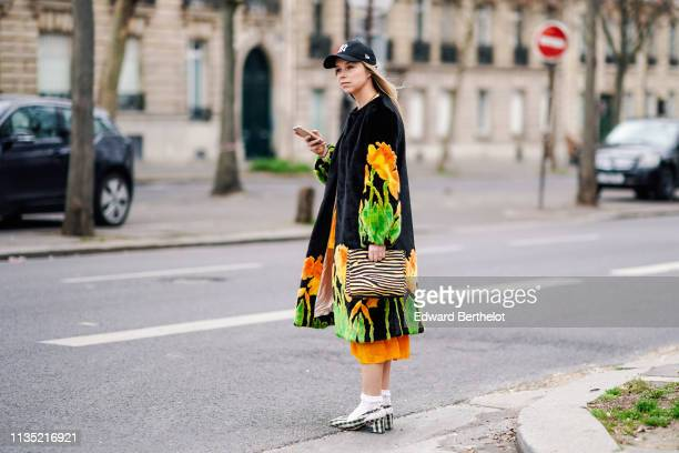 A guest wears a NY black cap a black fluffy coat with yelloworange and green daffodils design an orange dress a yellow and black zebra pattern bag...