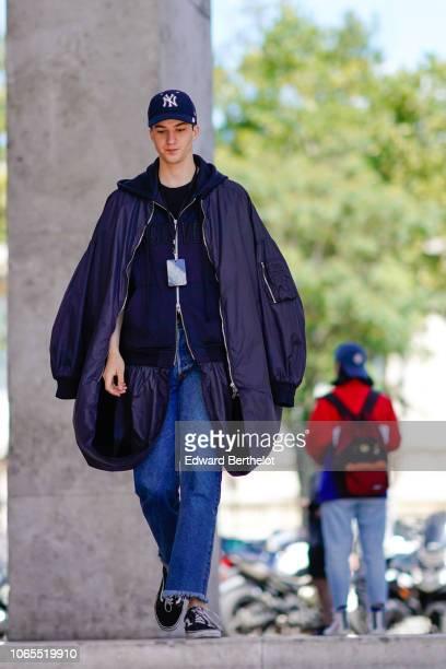 A guest wears a NY cap an oversized jacket blue denim pants outside Juun J during Paris Fashion Week Menswear SpringSummer 2019 on June 22 2018 in...