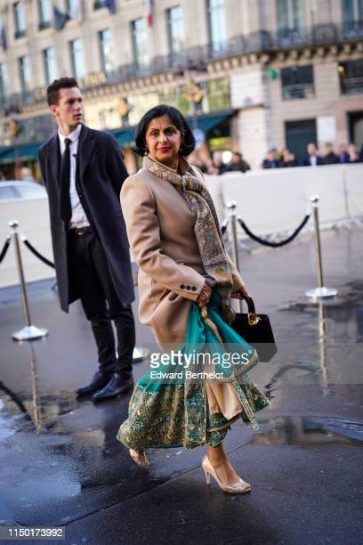 A guest wears a paisleydesign scarf a beige coat a green embroidered and goldthreaded sari golden peeptoe pumps outside the Opera Garnier 350th...