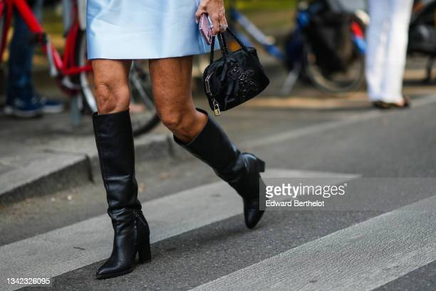 Guest wears a pale blue shiny silk short dress, a black handbag with a black sequins teddy beard embroidered, black shiny leather pointed heels knees...