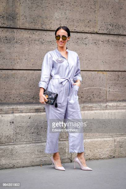 A guest wears a pale blue silk pyjama outfit a bag white heels shoes outside Elie Saab during Paris Fashion Week Haute Couture Fall Winter 2018/2019...