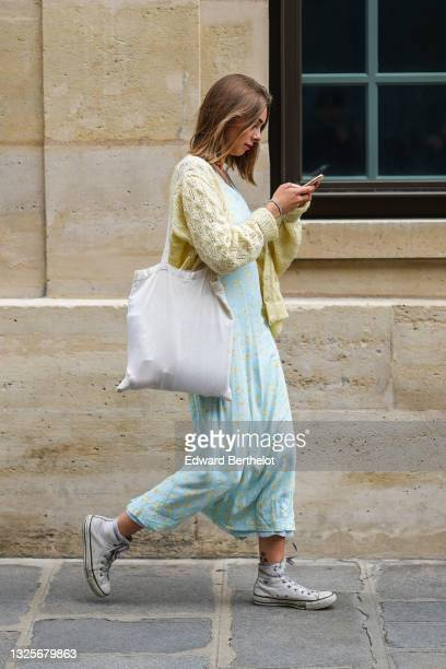 Guest wears a pale blue with yellow flower patterns midi dress, white Converse All Star sneakers, a white cotton shoulder bag, a pale yellow wool...