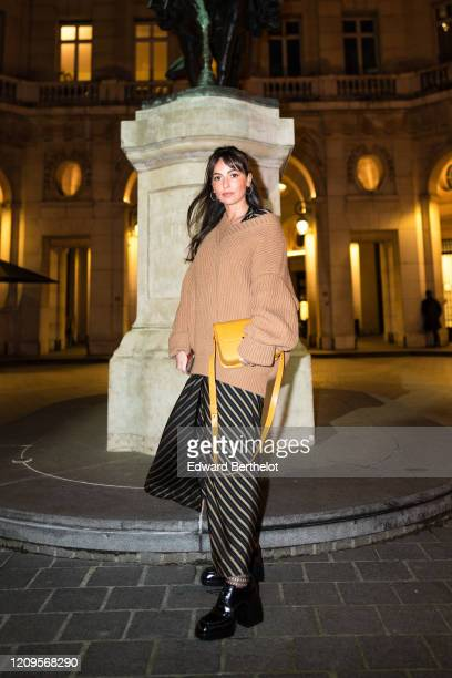 A guest wears a pale brown vneck oversized wool pullover a yellow bag a striped skirt black leather shoes earrings outside the MyTheresa x Amina...