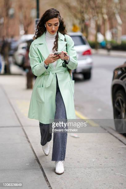 A guest wears a pale green trench coat a white turtleneck pullover gray jeans white shoes during New York Fashion Week Fall Winter 2020 on February...