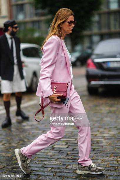 Guest wears a pale pink blazer jacket, matching pale pink suit flared pants, a silver pendant necklace, a red shiny leather crossbody bag with a gold...