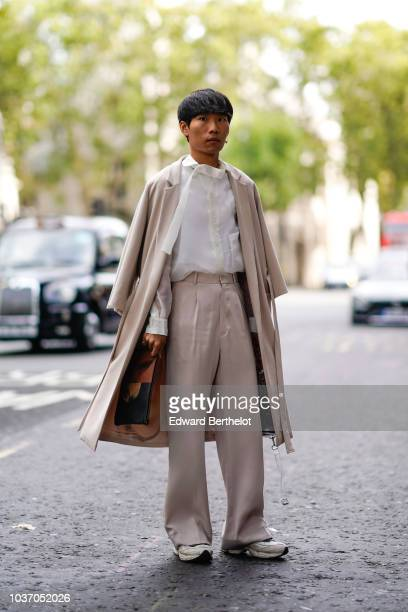 A guest wears a pale pink coat flared pants a white shirt sneaker shoes during London Fashion Week September 2018 on September 14 2018 in London...