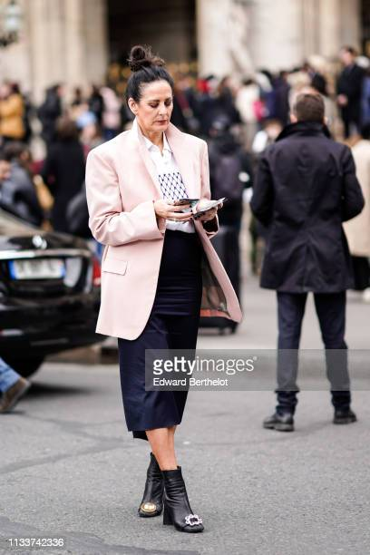 A guest wears a pale pink jacket black short pants black ankle boots outside Stella McCartney during Paris Fashion Week Womenswear Fall/Winter...