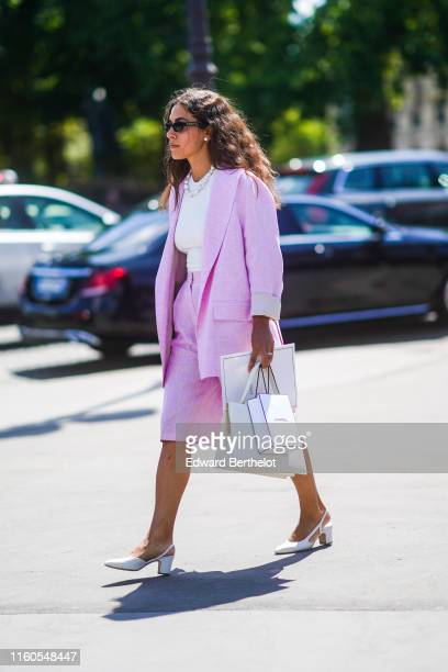 A guest wears a pale purple blazer jacket a white top a skirt a Chanel paper bag white shoes a pearl necklace earrings Chanel sunglasses outside...