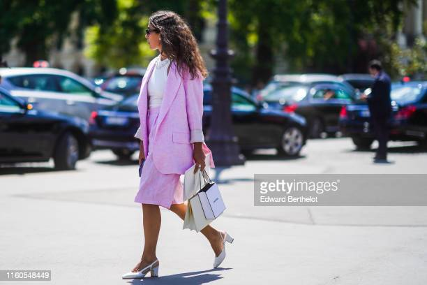 Guest wears a pale purple blazer jacket, a white top, a skirt, a Chanel paper bag, white shoes, a pearl necklace, earrings, Chanel sunglasses,...