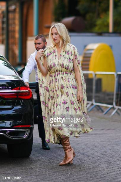 Guest wears a pale yellow gathered dress with pink roses pattern, brown pointy boots, during London Fashion Week September 2019 on September 15, 2019...