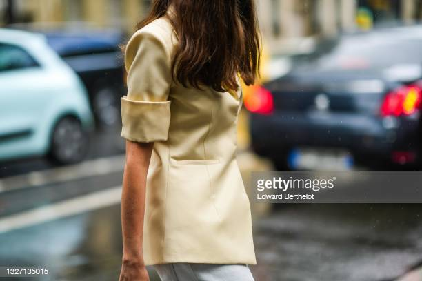 Guest wears a pale yellow rolled-up sleeves blazer jacket, a white denim jeans flared pants from Off-White, outside Off-White, as part of Paris...