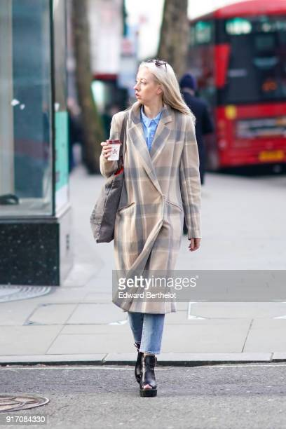 A guest wears a pattern coat cropped jeans black shoes holds a cup of coffee during London Fashion Week Men's January 2018 at on January 6 2018 in...