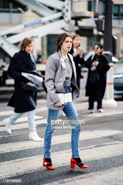 Guest wears a pearl necklace, a grey sweater, a grey Prince of Wales check jacket, jeans, red Miu Miu shoes, outside Miu Miu, during Paris Fashion...
