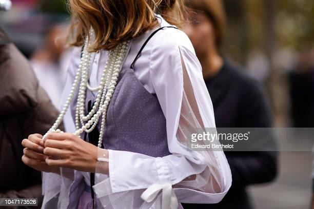 A guest wears a pearl necklace a pink lace dress outside Akris during Paris Fashion Week Womenswear Spring/Summer 2019 on September 30 2018 in Paris...