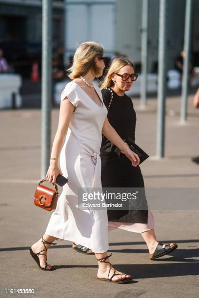 Guest wears a pearl necklace, a plunging neckline white long dress with a bow belt, a brown Chloe handbag, black gladiator flat sandals, outside...